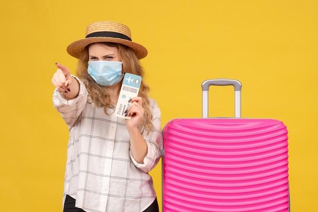 Vista frontale del pensiero giovane donna che indossa la maschera che mostra il biglietto e in piedi vicino alla sua borsa rosa che punta in avanti sul giallo