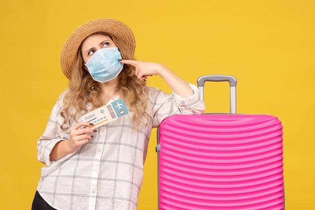 Vista frontale del pensiero giovane donna che indossa la maschera che mostra il biglietto e in piedi vicino alla sua borsa rosa