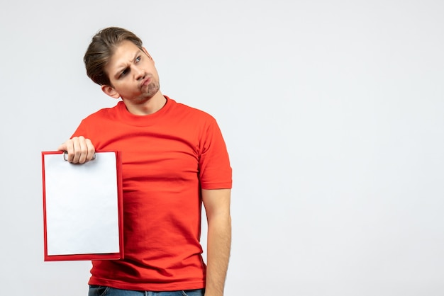 Front view of thinking young man in red blouse holding document on white background