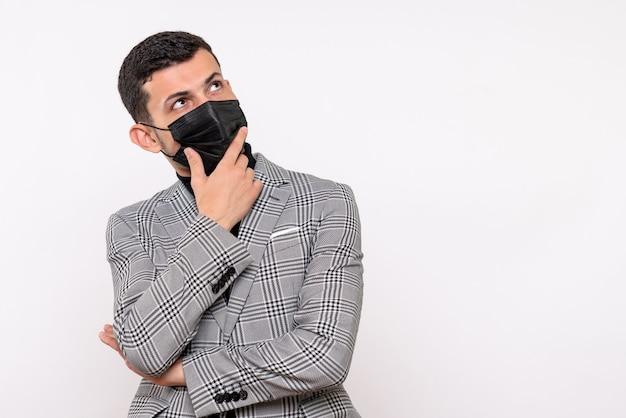 Vista frontale pensando giovane uomo con maschera nera in piedi su sfondo bianco isolato