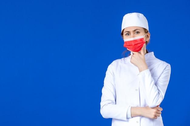 青い壁に赤いマスクと医療スーツの若い看護師を考える正面図