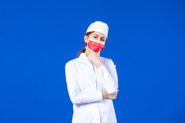 青い壁に赤い保護マスクと医療スーツの若い看護師を考える正面図