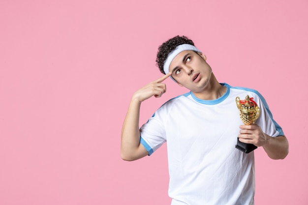 Front view thinking young player in sport clothes with golden cup