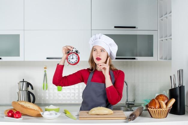 キッチンで赤い目覚まし時計を保持している若い女性を考える正面図