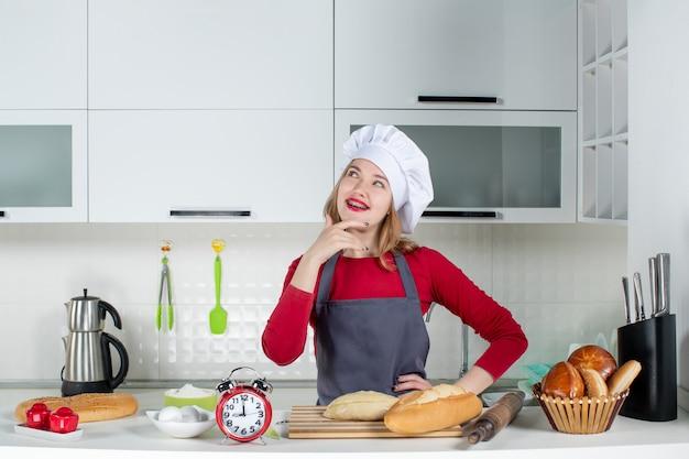 料理の帽子とエプロンで若い女性が台所で彼女の腰に手を置いて考える正面図