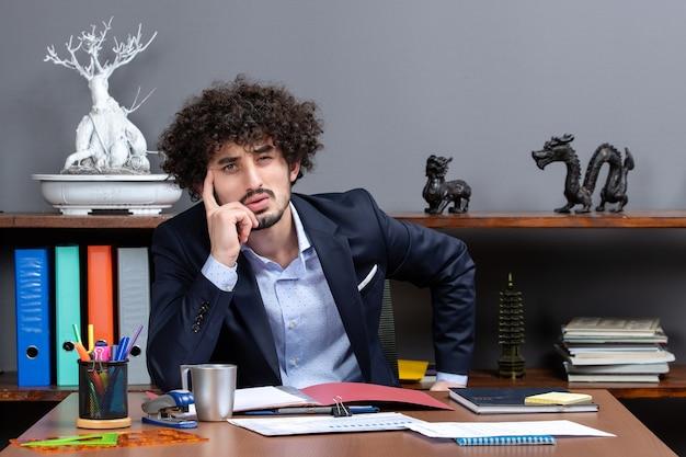 Vista frontale dell'uomo d'affari premuroso seduto alla sua scrivania in ufficio