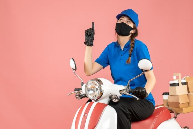 Vista frontale della premurosa ragazza del corriere che indossa maschera medica e guanti seduti su uno scooter che consegna ordini su sfondo color pesca pastello