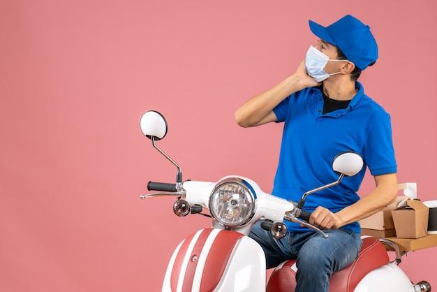 Vista frontale dell'uomo premuroso corriere in maschera medica che indossa cappello seduto su scooter su sfondo pesca pastello