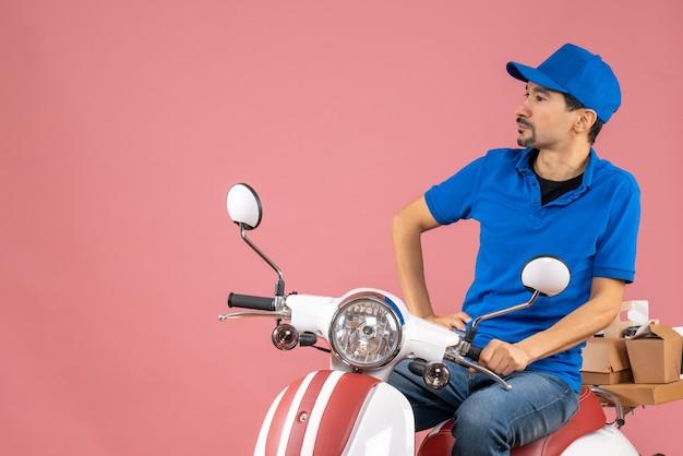 Vista frontale del ragazzo delle consegne premuroso che indossa un cappello seduto su uno scooter su sfondo color pesca pastello