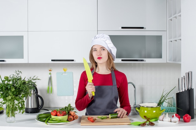 Front view thoughtful female cook in apron holding knife