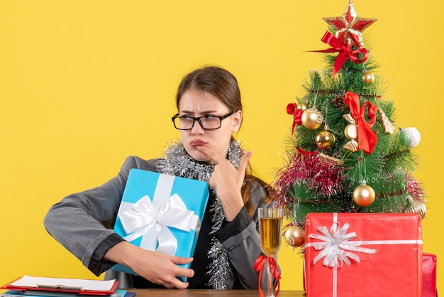 Ragazza premurosa vista frontale con gli occhiali seduto al tavolo mettendo il dito