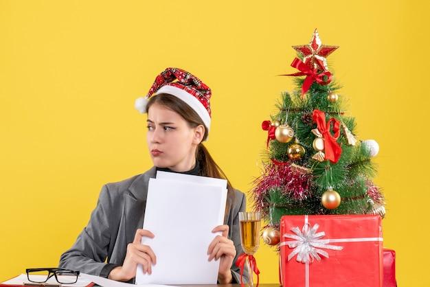 右のクリスマスツリーとギフトカクテルを見てテーブルに座っているクリスマス帽子を持つ正面図思慮深い女の子
