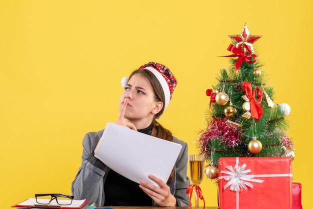 指を置いてテーブルに座っているクリスマスの帽子を持つ正面図思いやりのある女の子