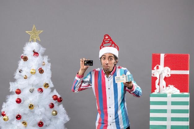 크리스마스 트리와 선물 주위에 카드와 여행 티켓을 들고 전면보기 사려 깊은 남자