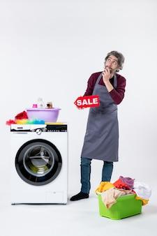 Vista frontale uomo premuroso che sostiene il cartello di vendita in piedi vicino al cesto della biancheria della lavatrice sul muro bianco