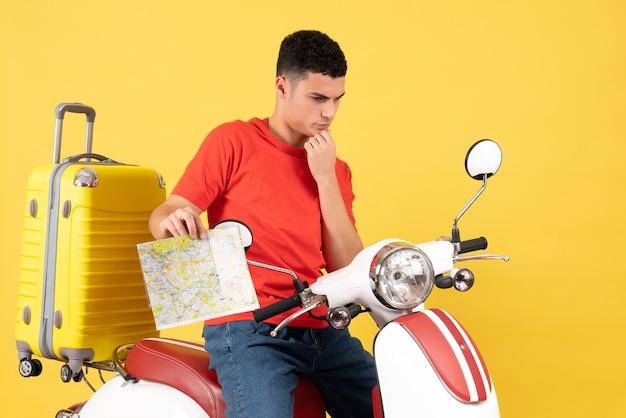 Вид спереди вдумчивый человек на мопеде с картой