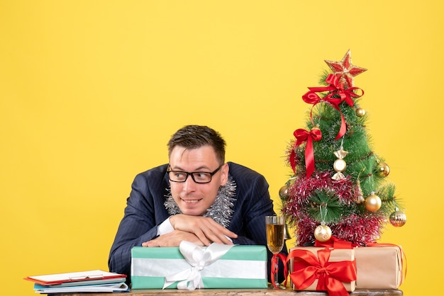Front view of thoughtful man putting head on gift box sitting at the table near xmas tree and presents on yellow