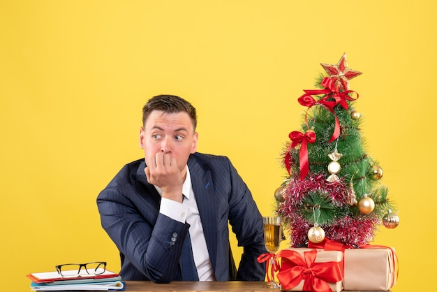 Front view of thoughtful man sitting at the table near xmas tree and presents on yellow