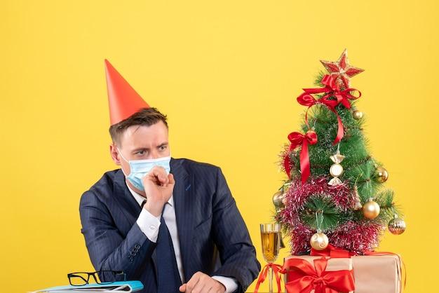Vista frontale dell'uomo premuroso con mascherina medica che si siede al tavolo vicino all'albero di natale e presenta su giallo