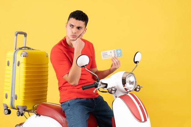 Вид спереди вдумчивый молодой мужчина в повседневной одежде на мопеде с билетом