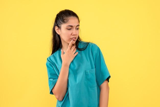 黄色の背景に立っている正面図思慮深いきれいな女性医師