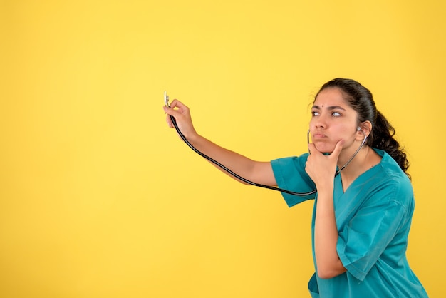 Vista frontale premurosa donna medico in uniforme utilizzando uno stetoscopio su sfondo giallo