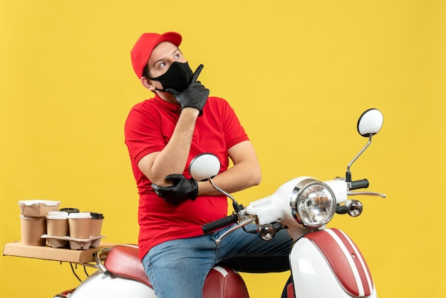 Vista frontale del giovane adulto premuroso che indossa la camicetta rossa e guanti del cappello nella mascherina medica che trasporta l'ordine che si siede sul motorino su fondo giallo