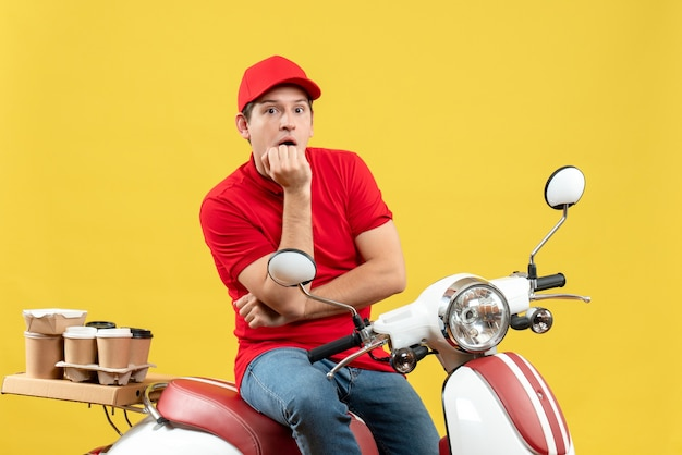 Front view of thoughtful young guy wearing red blouse and hat delivering orders on yellow background