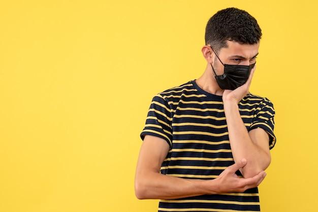 Вид спереди вдумчивый молодой человек в черно-белой полосатой футболке на желтом изолированном фоне