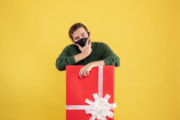 노란색에 큰 giftbox 뒤에 서있는 검은 마스크와 전면보기 사려 깊은 젊은 남자