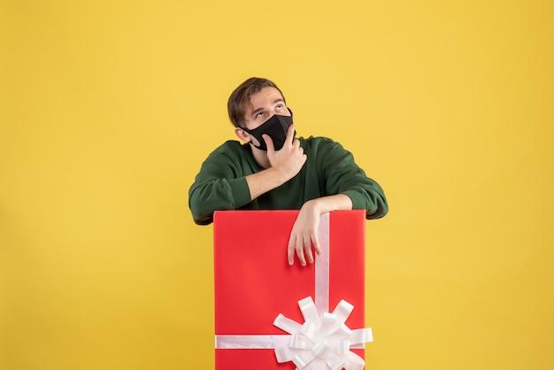 Giovane premuroso di vista frontale con la maschera nera che sta dietro il grande giftbox su giallo
