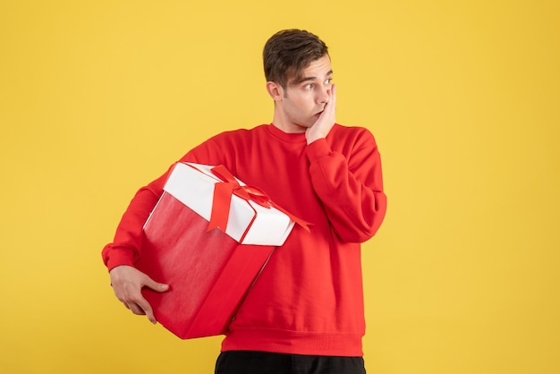 Front view thoughtful young man with red sweater standing on yellow