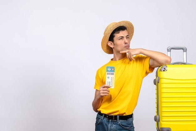 노란색 가방 티켓을 들고 근처에 서있는 노란색 티셔츠에 전면보기 사려 깊은 젊은 관광