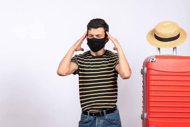 Vista frontale premuroso giovane turista con maschera nera in piedi vicino a valigia rossa tenendo la testa tra le mani