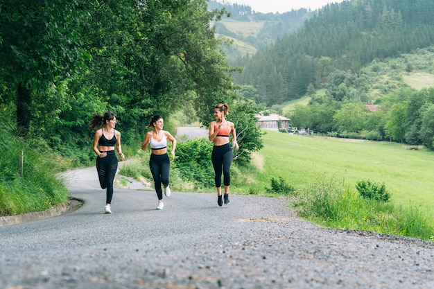 Front view of three beautiful happy women running along a road through a beautiful green forest with lots of trees