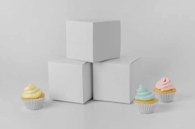 Front view of three cupcakes with packaging boxes