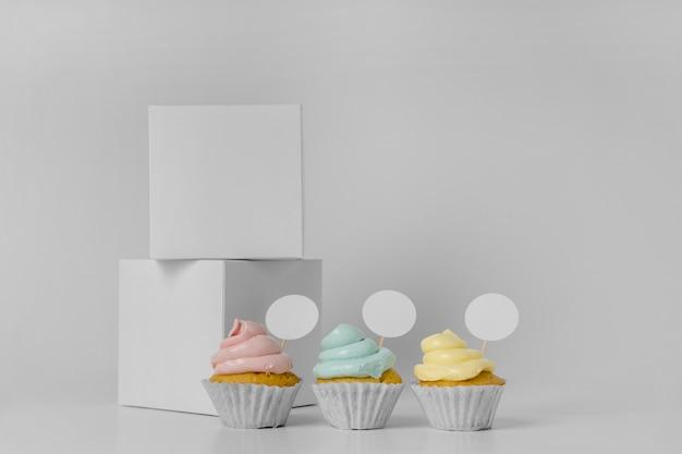 Vista frontale di tre cupcakes con scatole di imballaggio