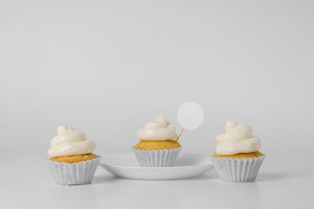 Vista frontale di tre cupcakes con confezione