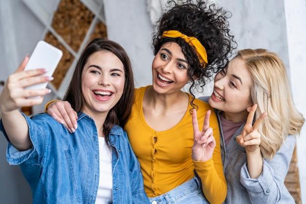 Vista frontale di tre donne felici che ridono e che prendono selfie