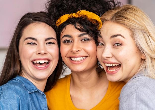 Vista frontale di tre donne felici che propongono insieme e sorridenti
