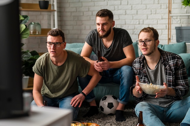Front view of three male friends watching sports on tv together while having beer and snacks