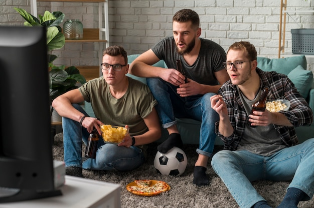Front view of three male friends watching sports on tv together while having snacks and beer