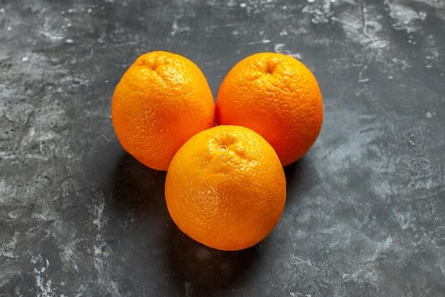Vista frontale di tre arance fresche biologiche naturali su sfondo scuro