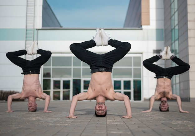 Front view of three shirtless hip hop dancers standing on their heads
