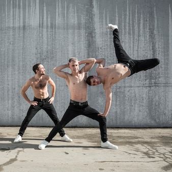 Front view of three shirtless hip hop performers posing outside