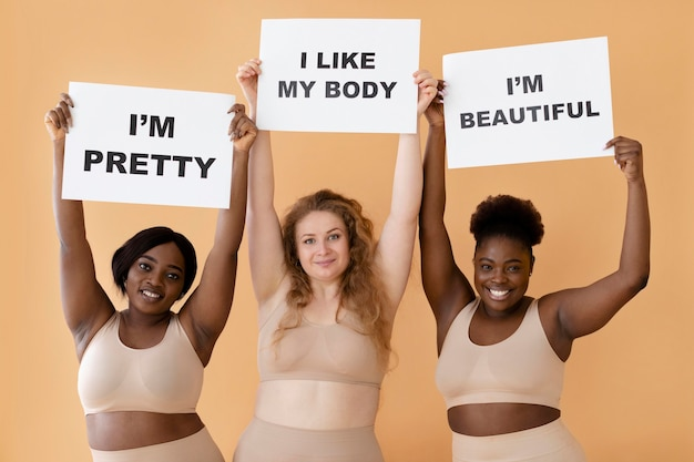 Front view of three women holding placards with body positivity statements