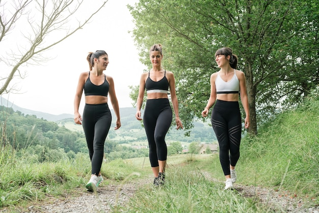 Front view three women talking and walking along a path through a forest before going for a run