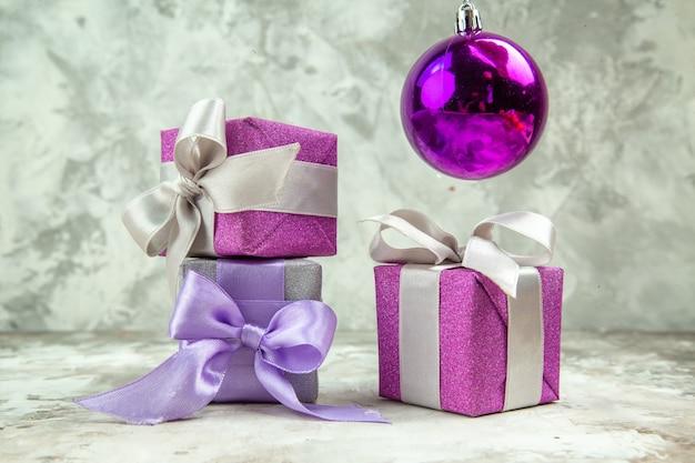 Vista frontale di tre regali di natale per i membri della famiglia e un accessorio decorativo su sfondo di ghiaccio