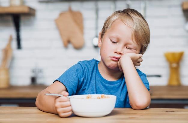 Вид спереди усталый мальчик пытается съесть его хлопья