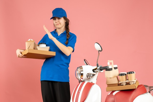 Vista frontale della ragazza stanca del corriere in piedi accanto alla moto con in mano caffè e piccole torte su sfondo color pesca pastello